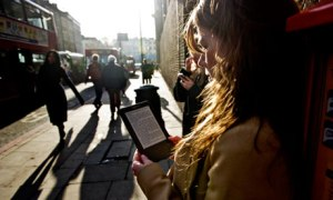 Woman reads ebook, Kindle in street