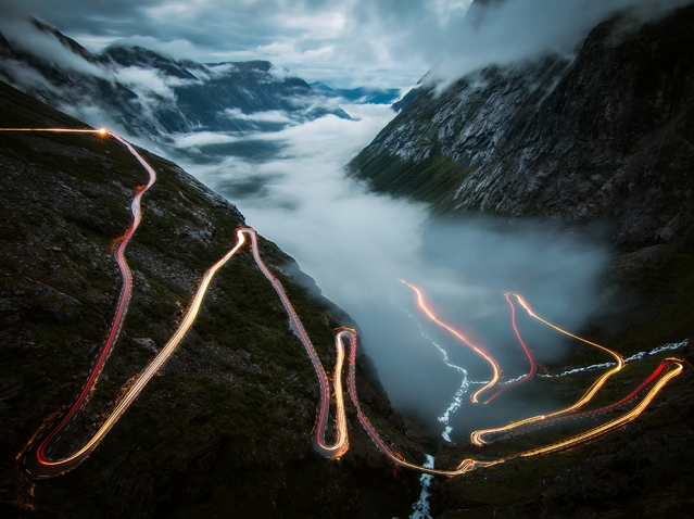 I took this photo in july 2014 at Trollstigen in Norway. Standing there alone in the fog, I was waiting for the view to become clear. And then it happened, the fog disappeared and though it was 1 am already, one car came slowly up the steep serpentines. It was my dream for a long time to take a photo of lighttrails like this in Norway - and it was just an awesome feeling that it worked out on the most beautiful and famous street. A few minutes later the fog returned, even thicker than before.